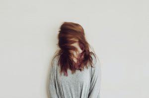 Frau schüttelt ihre langen, roten Haare