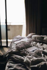 Hotelbett mit zerknitterter Decke und Buch