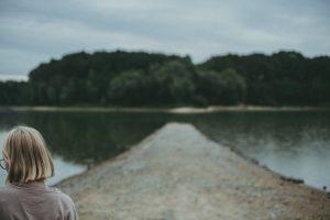 Kontemplativer Blick auf einen sommerlichen See mit Frau im Vordergrund