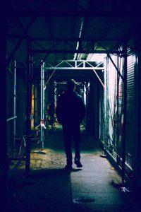 Mann geht im dunkeln unter einem Baugerüst durch die Stadt