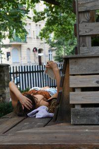 Frau liest ein Buch auf einer Parkbank mitten in Berlin