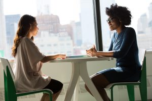 Arbeit: POC und Schwarze Frau sitzen sich am Tisch gegenüber