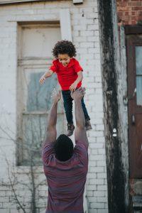 Schwarzer Vater wirft ein Schwarzes Kind in die Luft und fängt es auf