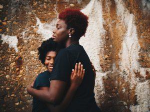 Zwei Schwarze Frauen umarmen sich