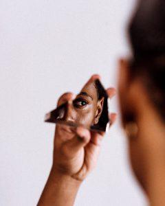 Schwarze Frau schaut in zerbrochenen Spiegel